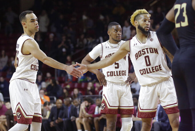 From left to right, Boston College's Jordan Chatman, Wynston Tabbs and Ky Bowman, celebrate after Bowman scored an a free throw in the second half of an NCAA college basketball game against Florida State, Sunday, Jan. 20, 2019, in Boston. (AP Photo/Steven Senne)