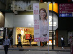 In this photo taken Thursday, Nov. 7, 2019, people walk past the campaign banner for district council candidate Cathy Yau at Causeway Bay in Hong Kong. Yau. a former police officer, grew exasperated as police used more force to quell the unrest. She quit the force in July after 11 years and is running in Sunday's district polls that are widely expected to deliver a decisive victory for the six-month-old movement seeking democratic reforms in the semi-autonomous Chinese territory. (AP Photo/Dita Alangkara)