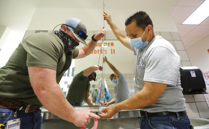 Wearing masks amid the concern of COVID-19, Richardson Independent School District workers Rogelio Ponciano, right, and Matt Attaway install a plexiglass barrier on the sink in the restroom for students at Bukhair Elementary School in Dallas, Wednesday, July 15, 2020. (AP Photo/LM Otero)