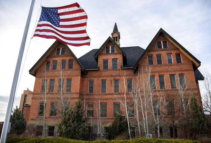 In this April 2, 2021, photo, an American flag flies at half-staff in front of Montana Hall at Montana State University in Bozeman, Mont. The flag was at half-staff in honor of the victims of an attack at the U.S. Capitol that day. The Montana University System is looking at neighboring states and seeking public input as it prepares to allow concealed firearms on campuses beginning on June 1, as required under a bill signed by Republican Gov. Greg Gianforte. (Rachel Leathe/Bozeman Daily Chronicle via AP)