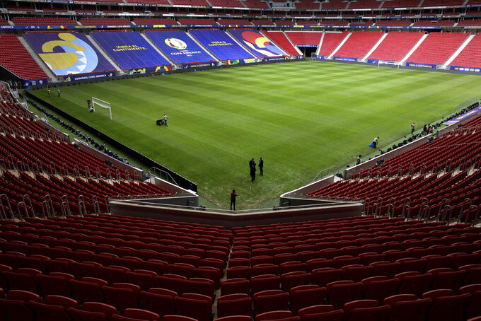 Employees prepare the National Stadium for the Copa America soccer tournament in Brasilia, Brazil, Friday, June 11, 2021. The stadium will host the opening game on June 13. (AP Photo/Eraldo Peres)