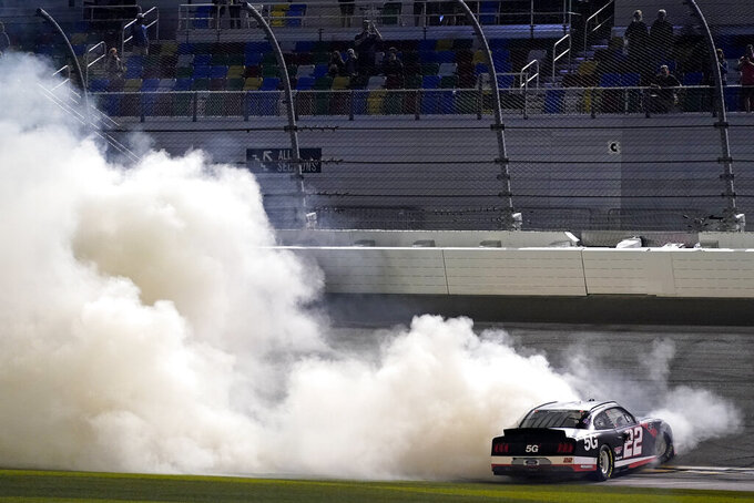 Austin Cindric (22) does a burnout in front of the grandstands as he celebrates winning the NASCAR Xfinity Series auto race at Daytona International Speedway, Saturday, Feb. 13, 2021, in Daytona Beach, Fla. (AP Photo/John Raoux)