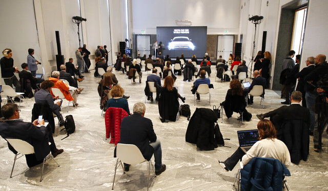 People sit a recommended distance apart from each other during the presentation of the new FIAT 500 electric n Milan, Italy, Wednesday, March 4, 2020. Countries are taking drastic and increasingly visible measures to curb the new coronavirus that first emerged in China and was spreading quickly through Europe, the Mideast and the Americas. (AP Photo/Antonio Calanni)