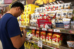 In this Oct. 2, 2019, photo, s Chinese tourist looks at a pack of crickets named HiSo snacks at a supermarket in Bangkok, Thailand. Insects have long been part of the diet of poor rural Thais, but entrepreneur Thatnat Chanthatham - inspired by studies showing bugs are high in protein and raising them does minimal damage to the environment - hopes to broaden the market for baked bugs by packaging them like potato chips and selling them in convenience store and supermarkets. (AP Photo/Sakchai Lalit)