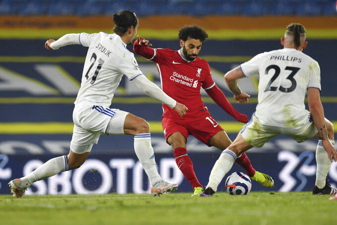 Liverpool's Mohamed Salah, center, is challenged by Leeds United's Pascal Struijk, left and Leeds United's Kalvin Phillips during the English Premier League soccer match between Leeds United and Liverpool at the Elland Road stadium in Leeds, England, Monday, April 19, 2021. (Paul Ellis/Pool via AP)