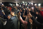 In this Tuesday, Dec. 10, 2019 photo, audience members hold their smartphones aloft after a performance of Les Miserables in at an outdoor event space in Hong Kong. A Hong Kong theater troupe is making audiences weep by touring a stirring production of 'Les Miserables.' Based on Victor Hugo's tale of rebellion in 19th-century France, the rousing music and lyrics of struggle and resistance struck chords with audience members emotionally and physically drained after six months of protests that have convulsed the city. (AP Photo/John Leicester)