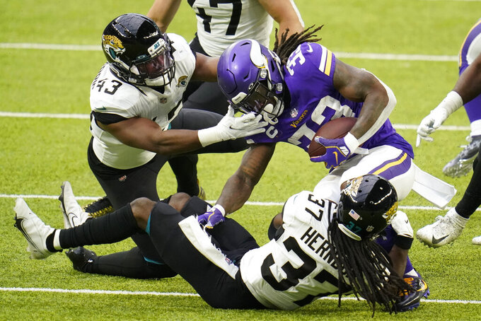 Minnesota Vikings running back Dalvin Cook (33) is tackled by Jacksonville Jaguars linebacker Joe Giles-Harris (43) and cornerback Tre Herndon (37) during the first half of an NFL football game, Sunday, Dec. 6, 2020, in Minneapolis. (AP Photo/Jim Mone)