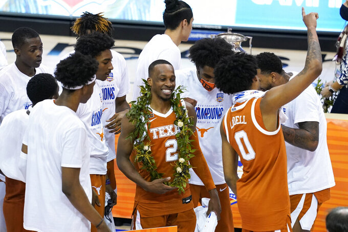 Texas guard Matt Coleman III (2) celebrates with teammates after they defeated North Carolina in an NCAA college basketball game for the championship of the Maui Invitational, Wednesday, Dec. 2, 2020, in Asheville, N.C. (AP Photo/Kathy Kmonicek)