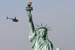 FILE - In this Jan. 21, 2018, file photo, a tourist helicopter circles the Statue of Liberty in New York. The PBS host Geoffrey Baer is back this summer with new episodes of his series