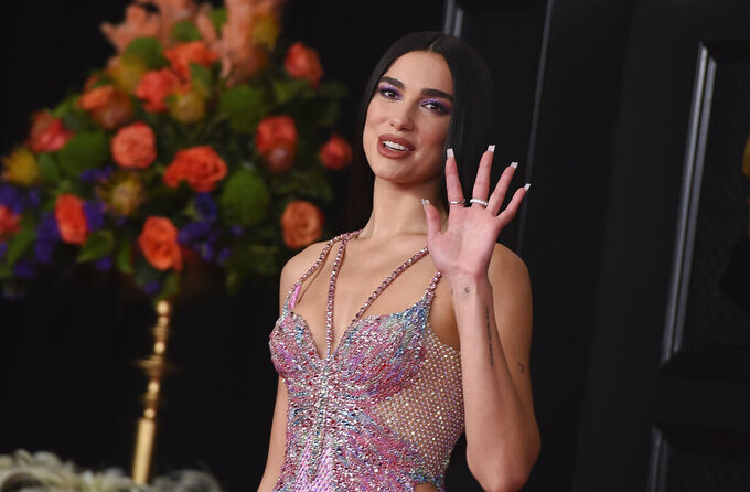 """FILE - In this Sunday, March 14, 2021 file photo, Dua Lipa arrives at the 63rd annual Grammy Awards at the Los Angeles Convention Center. British music's leading prize night next month will feature an audience of 4,000 people, in what will be the first major indoor music event in the country to welcome back a live audience since the coronavirus pandemic erupted more than a year ago. """"This has been a long tough year for everyone and I'm delighted the night will honor the key worker heroes who have cared for us so well during that time and continue to do so,"""" said singer/songwriter Dua Lipa, who is set to perform at the event. (Photo by Jordan Strauss/Invision/AP, File)"""