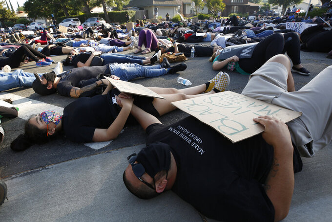 Aliana Gayton, left, holds hands with her father, Ronaldo Gayton, as they join other protesters Friday, June, 5, 2020, in lying down silently for 8 minutes and 46 seconds during a demonstration to honor George Floyd, near the home of Sacramento Mayor Darrell Steinberg in Sacramento, Calif. Floyd, a black man, died after being restrained by Minneapolis police officers on May 25. (AP Photo/Rich Pedroncelli)