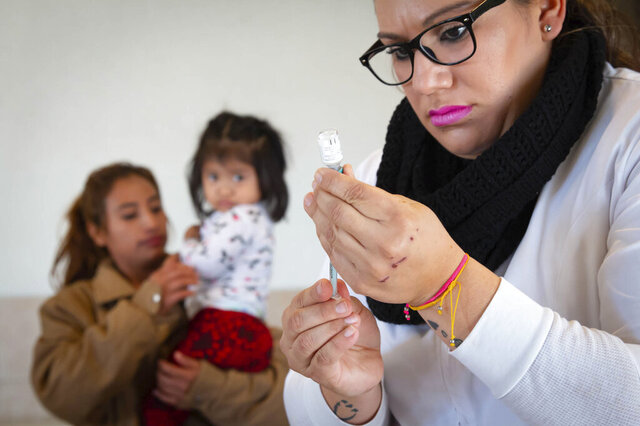 In this Jan. 28, 2020, photo provided by Cronkite News, Arizona State University, Andrea Ramirez, 2, of Chiapas, Mexico, watches Daniela Gastelum as she prepares a vaccine at Casa del Migrante in San Luis Rio Colorado, Mexico. One Hundred Angels, a Phoenix organization that provides medical care and other services to migrants, helped coordinate the one-day vaccination clinic at Casa del Migrante, working with the Mexican Red Cross. (Delia Johnson/Cronkite News, Arizona State University via AP)