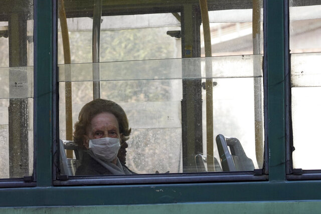 A woman wears a protective mask as she rides in a tram, in Rome, Wednesday, March 18, 2020. For most people, the new coronavirus causes only mild or moderate symptoms. For some it can cause more severe illness, especially in older adults and people with existing health problems. (AP Photo/Andrew Medichini)