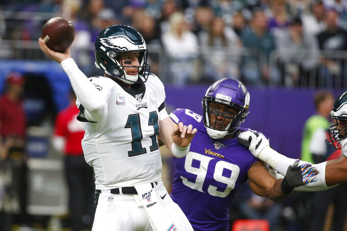 Philadelphia Eagles quarterback Carson Wentz, left, throws a pass as he is pressured by Minnesota Vikings defensive end Danielle Hunter (99) during the second half of an NFL football game, Sunday, Oct. 13, 2019, in Minneapolis. (AP Photo/Bruce Kluckhohn)