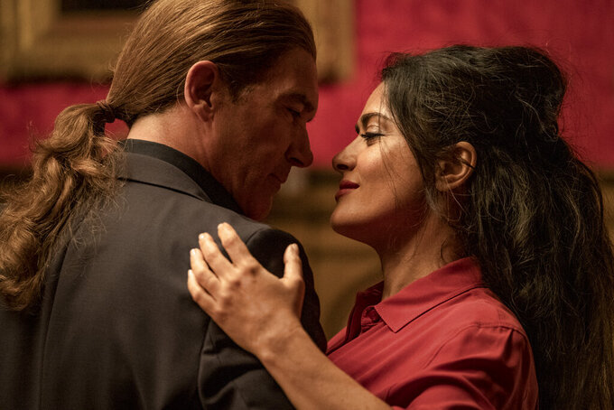 """This image released by Lionsgate shows Antonio Banderas, left, and Salma Hayek in a scene from """"The Hitman's Wife's Bodyguard."""" (David Appleby/Lionsgate via AP)"""