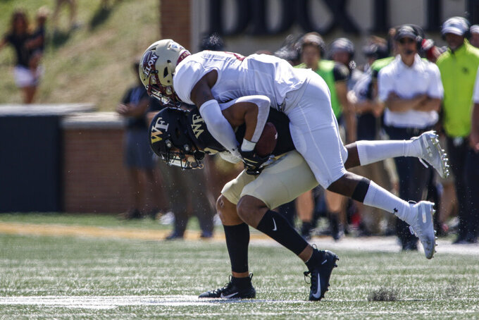 Wake Forest wide receiver Sage Surratt, left, keeps his balance as fights for yards as Elon defensive back Daniel Reid-Bennett tries to make the tackle in the first half of an NCAA college football game in Winston-Salem, N.C., Saturday, Sept. 21, 2019. (AP Photo/Nell Redmond)