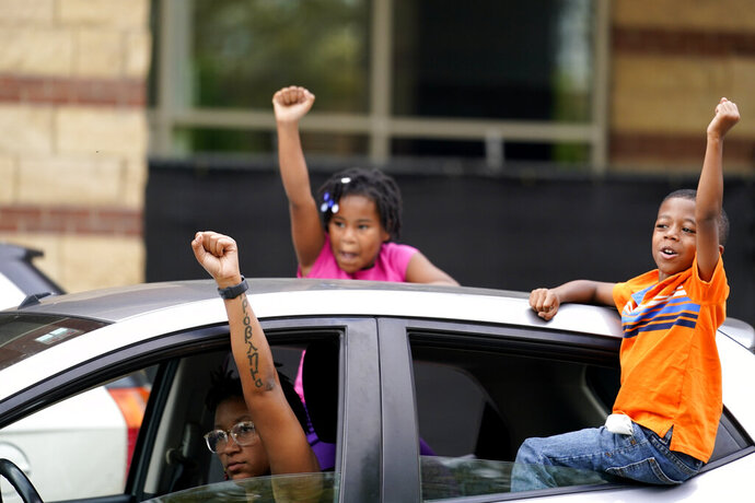 People in cars speak to protesters, Friday, Sept. 25, 2020, in Louisville. Breonna Taylor's family demanded Friday that Kentucky authorities release all body camera footage, police files and the transcripts of the grand jury hearings that led to no charges against police officers who killed the Black woman during a March drug raid at her apartment. (AP Photo/Darron Cummings)