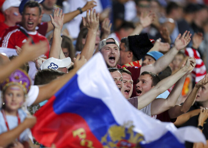 FILE - In this Friday, Oct. 11, 2019 filer, Russian fans cheer prior to the Euro 2020 group I qualifying soccer match between Cyprus and Russia at GSP stadium in Nicosia, Cyprus. With games scattered across 11 cities from London to Baku, this year's European Championship is going to be hard on the fans. Amid the coronavirus pandemic, it remains to be seen how many supporters will be able to attend matches or if any can follow their teams across borders into different countries. (AP Photo/Petros Karadjias, File)