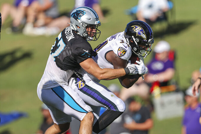 Baltimore Ravens running back Ty'Son Williams, right, fights for yards against Carolina Panthers linebacker Clay Johnston during a joint practice hosted by Carolina at the NFL football team's training camp in Spartanburg, S.C., Wednesday, Aug. 18, 2021. (AP Photo/Nell Redmond)