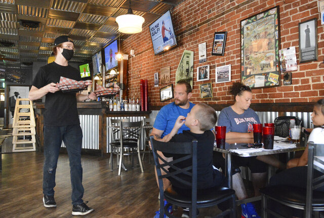 Tyler Vandermartin, bartender, left, carries sandwiches to a table at Wheel in Pottsville, Pa. on Tuesday, Sept. 8, 2020. Seated at the table, back, are Joshua Montesdeoca, Sr., left, and Tanazane Wood, right, both of Shenandoah, and seated at the table, front, from left, are Joshua Montesdeoca, Jr., 6, Gabriella Soto, 6, and Jessica Soto, not pictured, all of Shenandoah. Gov. Tom Wolf ordered that beginning Sept. 21, restaurants can increase their indoor occupancy to 50%, and alcohol sales must close at 10 p.m.. (Lindsey Shuey/Republican-Herald via AP)