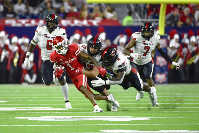 Houston wide receiver Nathaniel Dell (1) is tackled by Texas Tech linebacker Colin Schooler (17) and linebacker Brandon Bouyer-Randle (2) during the first half of an NCAA college football game Saturday, Sept. 4, 2021, in Houston. (AP Photo/Justin Rex)