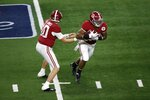 Alabama quarterback Mac Jones (10) hands the ball off to running back Najee Harris (22) in the first half of the Rose Bowl NCAA college football game against Notre Dame in Arlington, Texas, Friday, Jan. 1, 2021. (AP Photo/Roger Steinman)