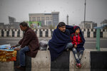 A farmer shares his shawl with a child as they sit on a road divider listening to a speaker during a protest against new farm laws at the Delhi-Uttar Pradesh state border, India, Friday, Jan. 8, 2021. (AP Photo/Altaf Qadri)