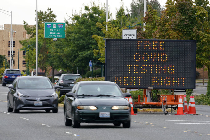 A sign directs motorists to a COVID-19 testing site, Wednesday, Sept. 22, 2021, in Tukwila, Wash., south of Seattle. (AP Photo/Ted S. Warren)