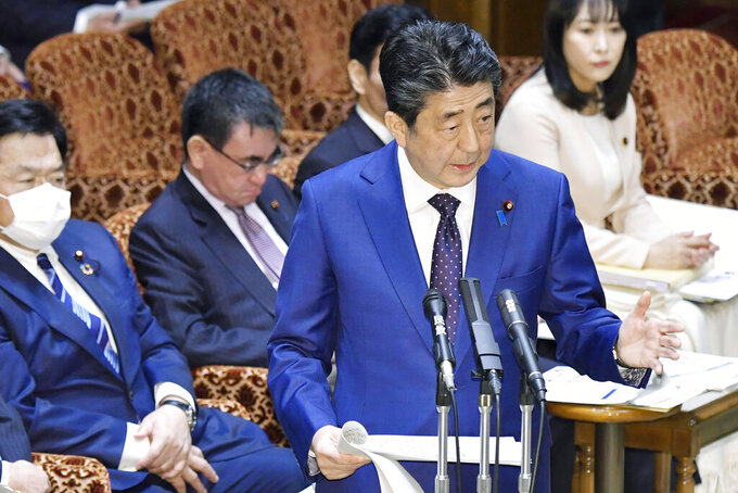 Japan's Prime Minister Shinzo Abe speaks at a parliamentary session in Tokyo Monday, March 23, 2020. Abe said a postponement of Tokyo Olympics would be unavoidable if the games cannot be held in a complete way because of the coronavirus pandemic. (Yoshitaka Sugawara/Kyodo News via AP)