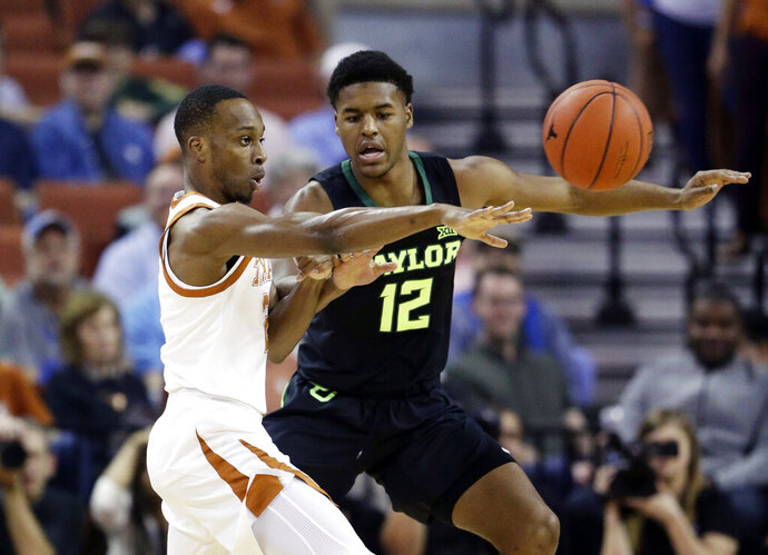Texas guard Courtney Ramey (3) passes the ball past Baylor guard Jared Butler (12) during the first half on an NCAA college basketball game Wednesday, Feb. 6, 2019, in Austin, Texas. (AP Photo/Eric Gay)