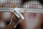 A steward uses a plastic glove and a cloth to disinfect the volleyball net during a rehearsal before the start of the volleyball preliminaries at Ariake Arena at the 2020 Summer Olympics, Friday, July 23, 2021, in Tokyo, Japan. (AP Photo/Frank Augstein)