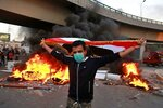 A protester holds an Iraqi flag while anti-government protests set fire while security forces fired live ammunition and tear gas near the state-run TV in Baghdad, Iraq, Monday, Nov. 4, 2019. (AP Photo/Khalid Mohammed)
