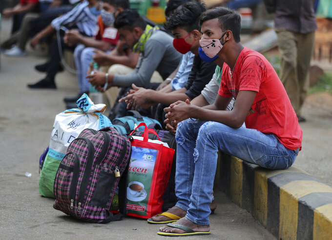 Travelers wait for outstation trains after authorities imposed a two-week lockdown to curb the rising number of COVID-19 cases in Bengaluru, India, Wednesday, April 28, 2021. India, a country of nearly 1.4 billion people, Wednesday became the fourth nation to cross 200,000 deaths. (AP Photo/Aijaz Rahi)