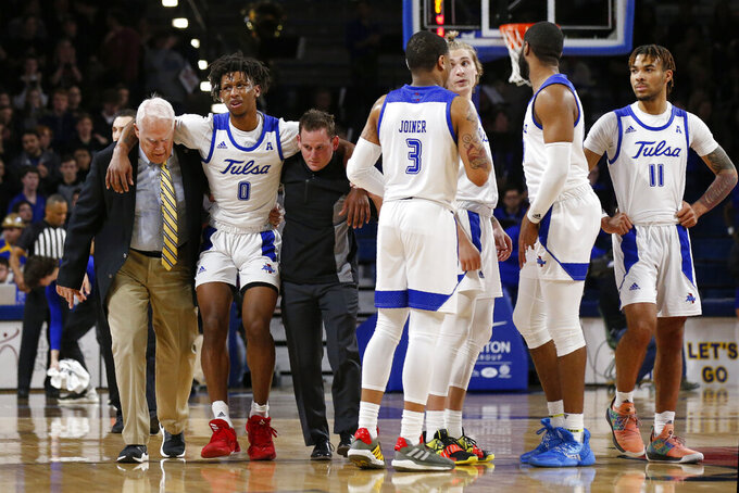 Tulsa guard Brandon Rachal (0) is helped off the court following an injury during the second half of the team's NCAA college basketball game against Connecticut in Tulsa, Okla., Thursday, Feb. 6, 2020. (AP Photo/Sue Ogrocki)