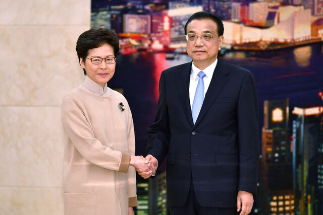 In this photo released by Hong Kong Government Information Services, Hong Kong Chief Executive Carrie Lam, left, and Chinese Premier Li Keqiang pose for a photo during a meeting in Beijing Monday, Dec. 16, 2019. Turmoil over amendments to extradition legislation has damaged Hong Kong society on all fronts, Li said Monday during a meeting with the semiautonomous territory's leader. It's her first visit to Beijing since pro-democracy candidates swept local Hong Kong elections last month in a rebuke of how Lam has handled months of fiery anti-government protests. (Hong Kong Government Information Services via AP)