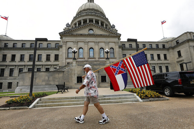 Don Hartness of Ellisville, walks around the Capitol carrying the current Mississippi state flag and the American flag, Saturday, June 27, 2020, in Jackson, Miss. A supporter of the current flag, Hartness wanted to make his position known to lawmakers as he walked around the building for several hours. The current state flag has in the canton portion of the banner the design of the Civil War-era Confederate battle flag, that has been the center of a long-simmering debate about its removal or replacement. (AP Photo/Rogelio V. Solis)