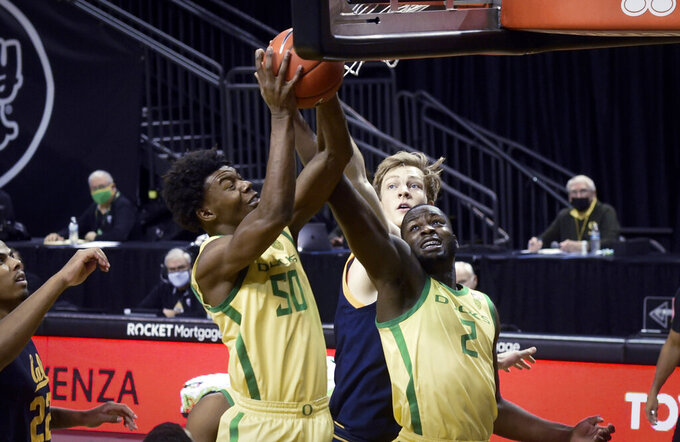 Oregon forward Eric Williams Jr. (50), California forward Lars Thiemann (21) and Oregon forward Eugene Omoruyi (2) reach for a rebound during the first half of an NCAA college basketball game in Eugene, Ore., Friday, Dec. 31, 2020. (AP Photo/Andy Nelson)