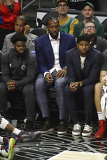 Los Angeles Clippers' Kawhi Leonard, center, and Paul George, right, watch from the bench during the second half of the team's NBA basketball game against the Milwaukee Bucks on Wednesday, Nov. 6, 2019, in Los Angeles. (AP Photo/Marcio Jose Sanchez)