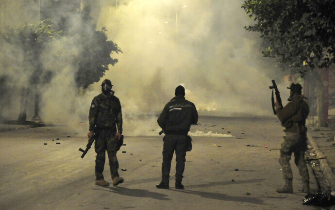 Police officers face demonstrators during clashes in Ettadhamen City near Tunis, Tunisia, Tuesday, Jan. 19, 2021. A growing groundswell of youth unrest, tapping into a well of economic frustration, is sweeping Tunisia and worrying its leadership all the way to the top. It is, after all, the country that triggered the 2011 Arab Spring revolutions. (AP Photo/Hassene Dridi)