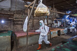 A health worker in protective gear sprays disinfectant in a traditional market to help curb the spread of the coronavirus in Medan, North Sumatra, Indonesia, Wednesday, Sept. 23, 2020. (AP Photo/Binsar Bakkara)
