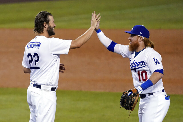 Los Angeles Dodgers starting pitcher Clayton Kershaw, left, high-fives Justin Turner after the team's 3-0 win over the Milwaukee Brewers in Game 2 of a National League wild-card baseball series Thursday, Oct. 1, 2020, in Los Angeles. (AP Photo/Ashley Landis)