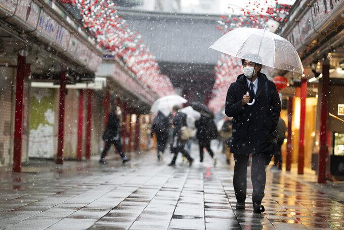 A man wearing a face mask walks through the Sensoji temple in the snow in Tokyo on Thursday, Jan. 28, 2021. (AP Photo/Hiro Komae)