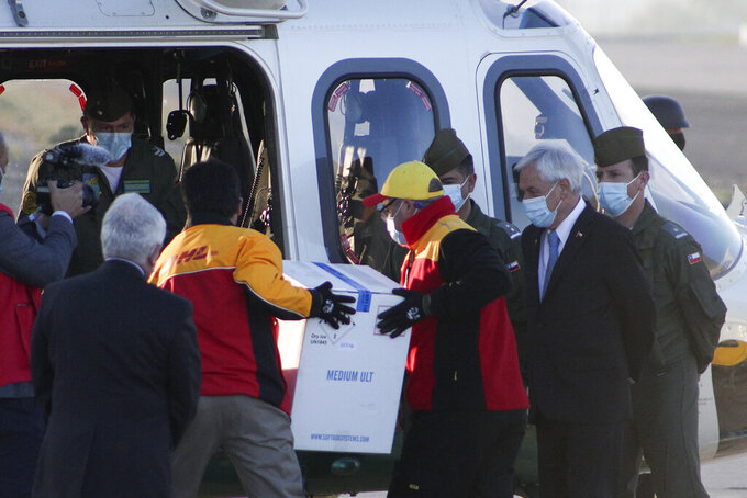 Chile's President Sebastian Pinera, second right, watches workers carry a box containing Pfizer COVID-19 vaccines to an helicopter for its distribution around the country at the Merino Benitez International Airport in Santiago, Chile, Thursday, Dec. 24, 2020. The first shipment of the Pfizer COVID-19 vaccine arrived to Chile early Thursday from Belgium. (AP Photo/Esteban Felix)