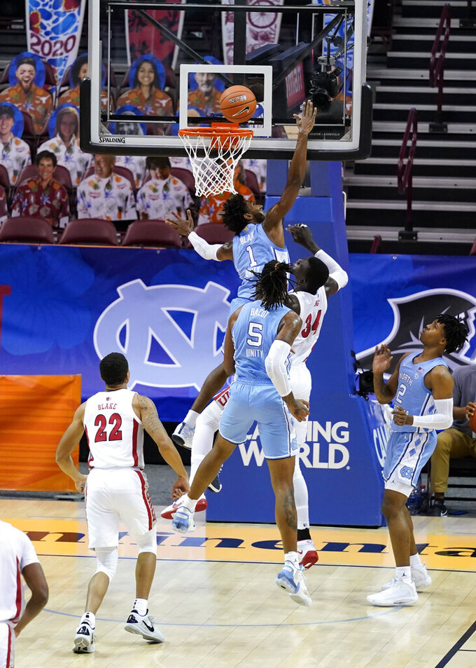 North Carolina guard Leaky Black (1) tries to block a shot by UNLV forward Cheikh Mbacke Diong (34) in the first half of an NCAA college basketball game in the Maui Invitational tournament, Monday, Nov. 30, 2020, in Asheville, N.C. (AP Photo/Kathy Kmonicek)
