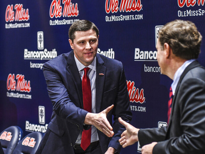 New Mississippi athletic director Keith Carter, left, shakes hands with search committee chairman Mike Glenn at a press conference at the Manning Center in Oxford, Miss., Friday, Nov. 22, 2019. (Bruce Newman/The Oxford Eagle via AP)