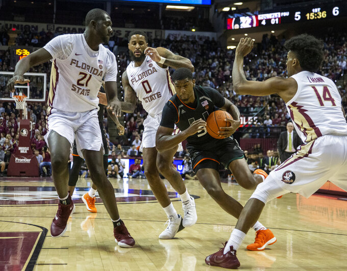 Miami guard Anthony Lawrence ll drives between Florida State center Christ Koumadje (21), forward Phil Cofer (0) and guard Terrance Mann in the first half of an NCAA college basketball game in Tallahassee, Fla., Wednesday, Jan. 9, 2019. (AP Photo/Mark Wallheiser)