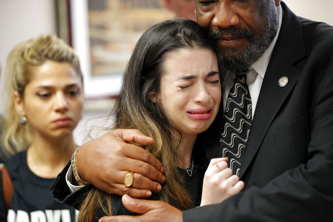 FILE- In this Feb. 21, 2018 file photo, Aria Siccone, 14, a student survivor from Marjory Stoneman Douglas High School massacre, cries as she recounts her story from that day, while state Rep. Barrinton Russell, D-Dist. 95, comforts her, as they talk to legislators at the state Capitol regarding gun control legislation, in Tallahassee, Fla. Even before the COVID pandemic upended the lives of millions of high school students, forever altering treasured milestones, homecomings, proms and graduation ceremonies, the Douglas high seniors were inextricably linked by tragedy. (AP Photo/Gerald Herbert, File)