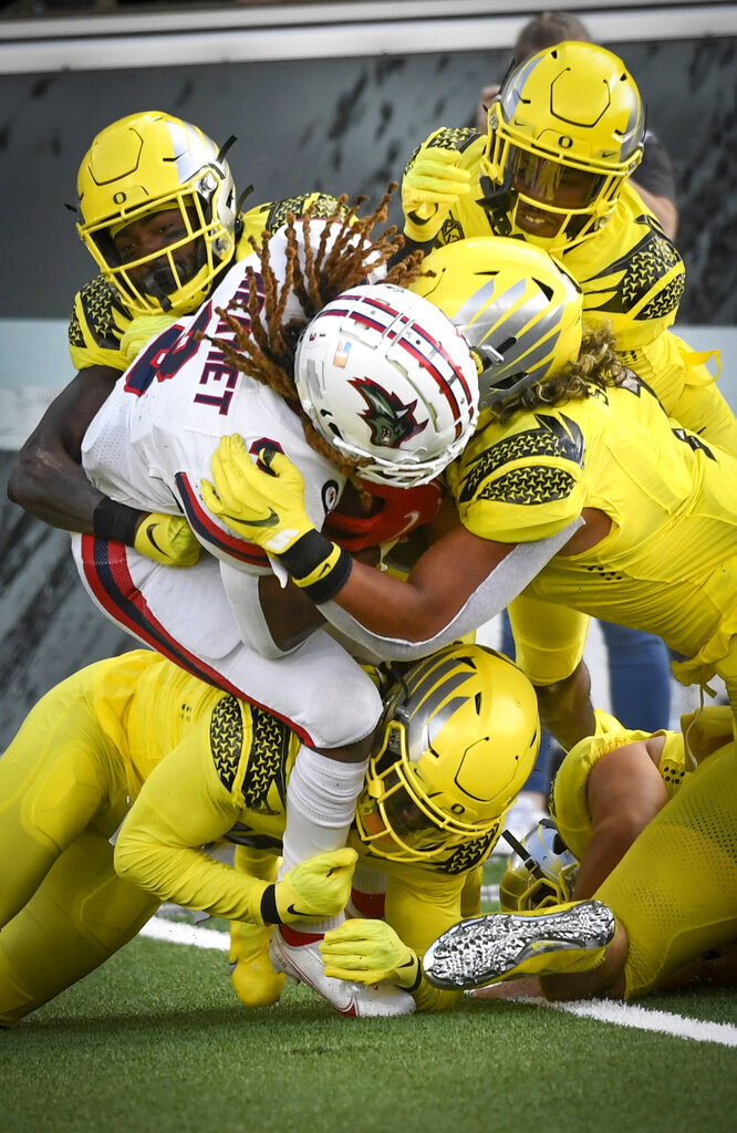 Stony Brook running back Seba Nekhet (3) is tackled by Oregon cornerback DJ James (0), cornerback Dontae Manning (8), Oregon linebacker Noah Sewell (1) and Oregon safety Jamal Hill (19) during the second quarter of an NCAA college football game Saturday, Sept. 18, 2021, in Eugene, Ore. (AP Photo/Andy Nelson)