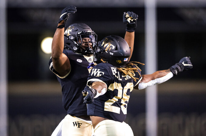 Wake Forest running back Christian Beal-Smith (26) his touchdown against Campbell with running back Kenneth Walker III during an NCAA college football game Friday, Oct. 2, 2020, in Winston-Salem, N.C. (Andrew Dye/The Winston-Salem Journal via AP)