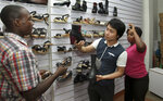 FILE - In this June 8, 2015, file photo, Chinese national Wei Kun, center, and his sales executive Allen Tushabe, right, sell a pair of shoes made in China to a customer at their shop in Kampala, Uganda. China's large-scale investments in Africa are starting to find pushback in Uganda. Some critics worry the East African nation is using oil it hasn't even begun to produce to borrow hundreds of millions of dollars for infrastructure projects. (AP Photo/Stephen Wandera, File)